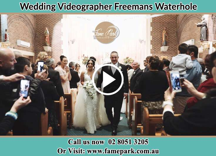 The newly weds walking through the well wishers Freemans Waterhole NSW 2323