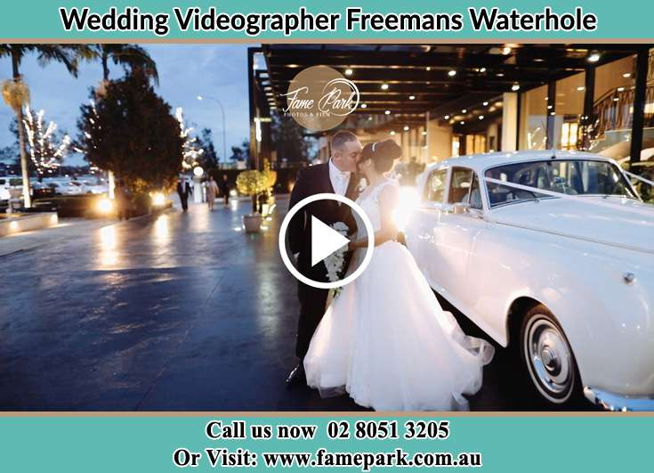 The newly weds kissing near the wedding car Freemans Waterhole NSW 2323