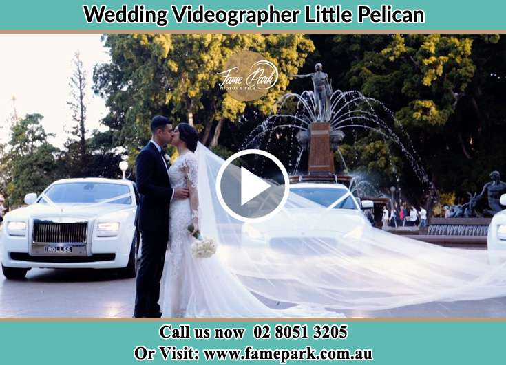 The new couple kissing near their wedding car Little Pelican NSW 2281
